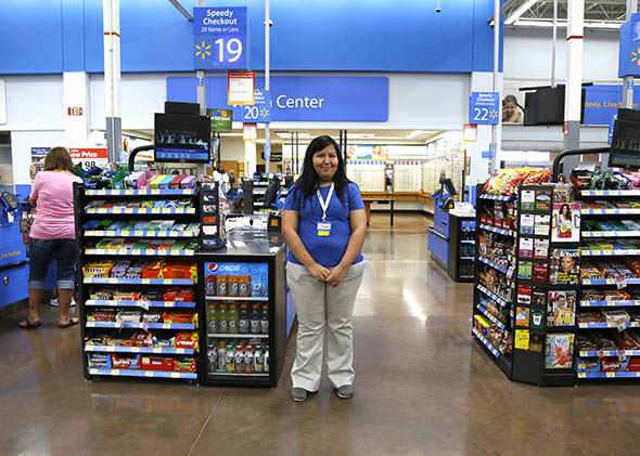 A cashier waits for customers at a Walmart Supercenter in Rogers