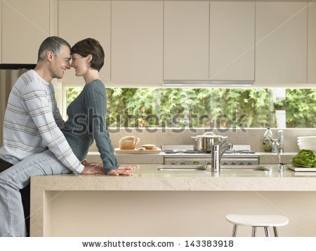 stock-photo-happy-couple-rubbing-noses-at-kitchen-counter-143383918